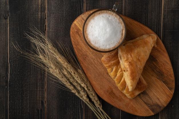 朝は完璧な朝食のコンセプトです。白いコーヒーカップと木製のテーブルの上の朝食のためのクロワッサン