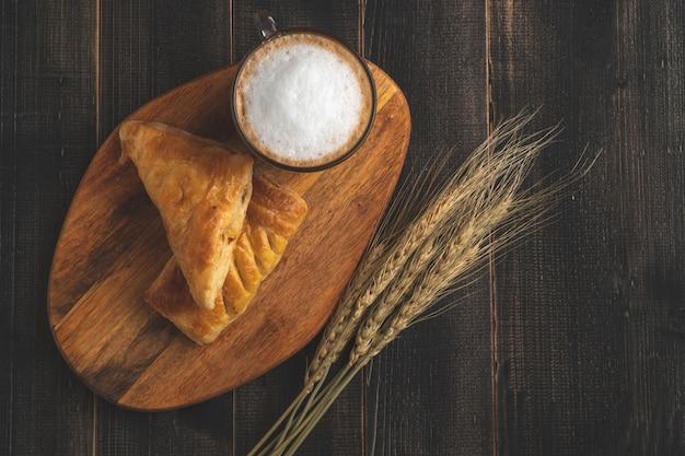 白いコーヒーカップとクロワッサンの木の朝食