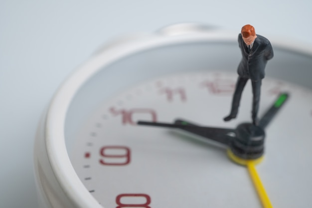 図のビジネスマンは、時間を示す時計の顔の近くに白い時計の顔の上に立って考え、立っています。