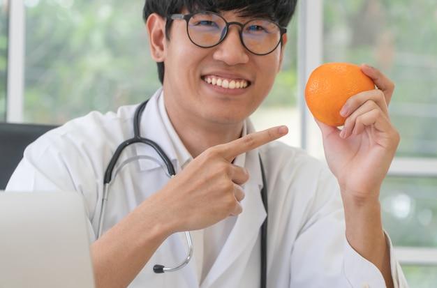 医師または栄養士がオレンジを持ち、オレンジに指を向けてクリニックで笑顔になります。