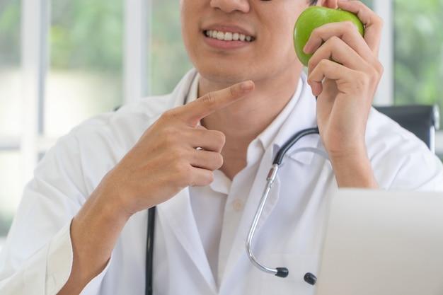 Врач или диетолог держат зеленое яблоко, указывают пальцем на яблоко и улыбаются в клинике.