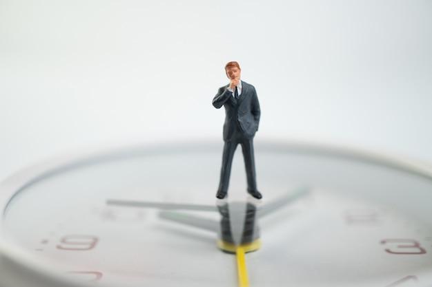 時間を示す時計の顔のそばに白い時計の顔の上に立っている図のビジネスマン。
