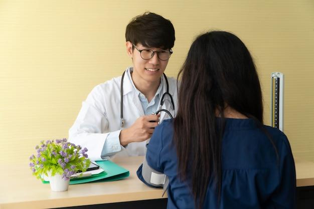 ハンサムで若い医者が患者に相談し、医療情報を説明します