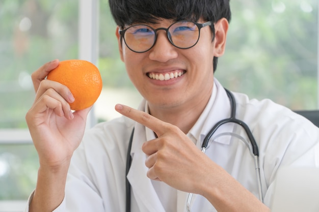 Врач или диетолог держите апельсин и указывайте пальцем на апельсин.