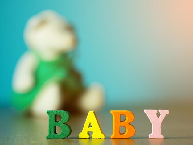 赤ちゃん。木製の手紙で作られた英語のアルファベット。