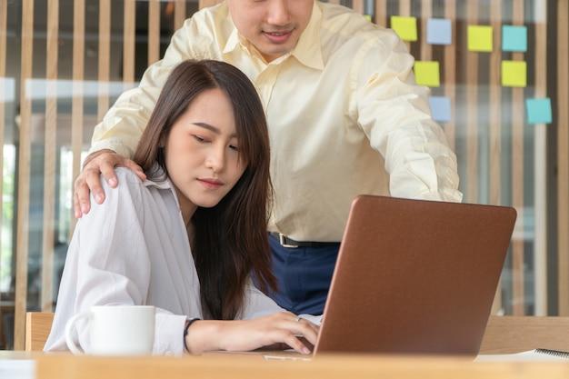職場のオフィスで女性従業員の肩に手を置くビジネスマン