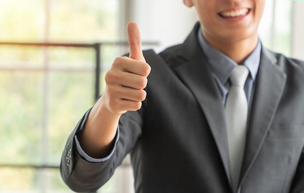 Выборочный фокус больших пальцев. молодой бизнесмен показывает палец вверх до успешного бизнеса.