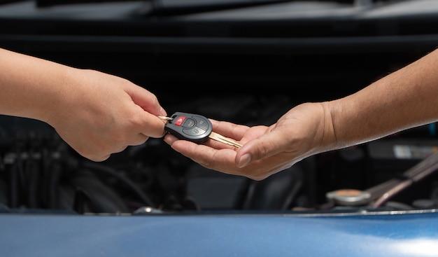 それを修復する車のエンジンの背景に車のエンジン修理工に車のキーを与える顧客の手のクローズアップ。