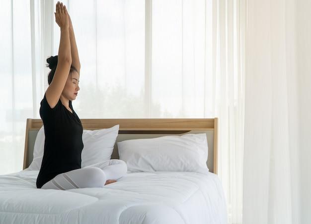 Средних лет женщины занимаются йогой в спальне утром