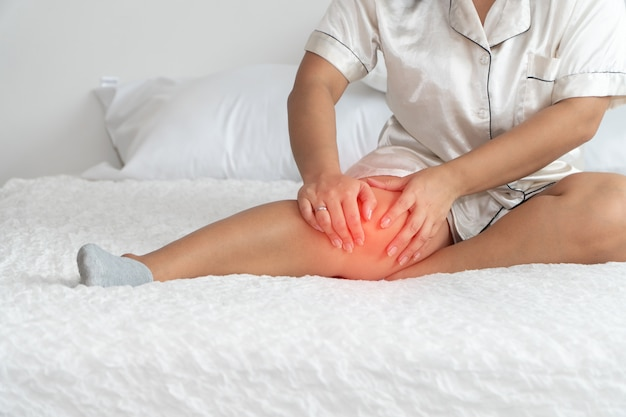 太りすぎの女性がベッドの上に座って、ひざをキャッチ