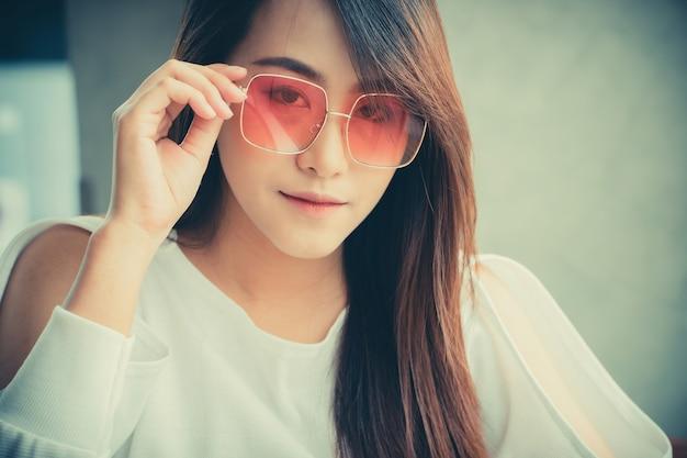 Азиатские солнечные очки носки женщины и сидеть в кофейне.