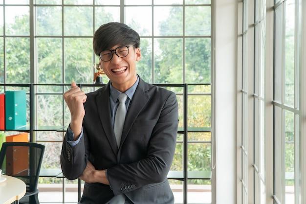 若いアジア系のビジネスマンは職場で幸せと祝う成功を興奮させた