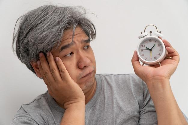 アジアの中年男性が白い目覚まし時計を持っていると、彼の顔は退屈と気分が悪くなった