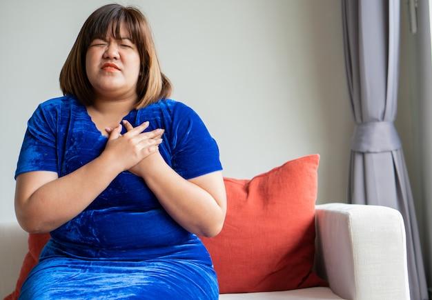 太りすぎのアジアの女性は、リビングルームのソファに座っています。