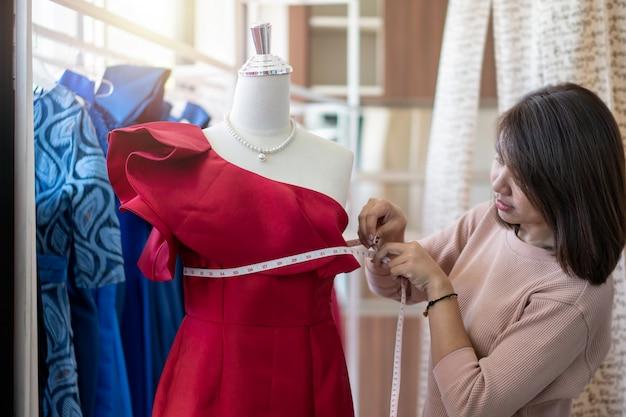 Размер азиатского модельера портнихи женщины измеряя размер манекена в выставочном зале. шитье и мода