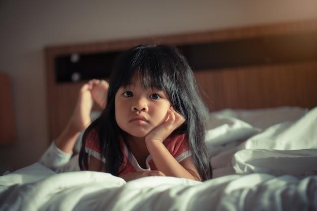 とても素敵で愛らしい少女は、ベッドで休憩し、テレビを見て