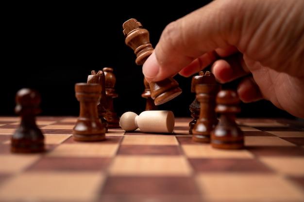 競争の成功プレイでチェス図を移動する自信を持って実業家の手のクローズアップ。
