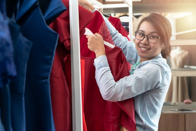 Счастливый молодой азиатский модельер портнихи женщины проверяет завершение для костюма и платья в выставочном зале.