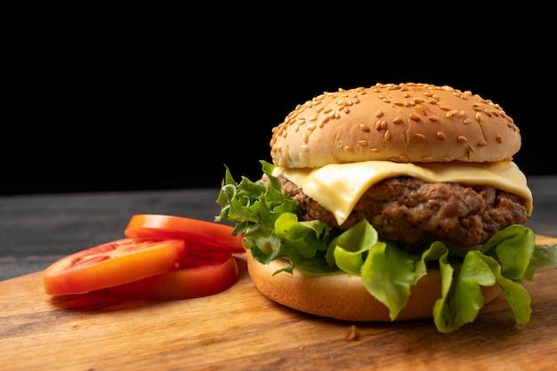まな板の上のスライストマトの横にある新鮮な野菜、チーズと新鮮なおいしい自家製ハンバーグ。