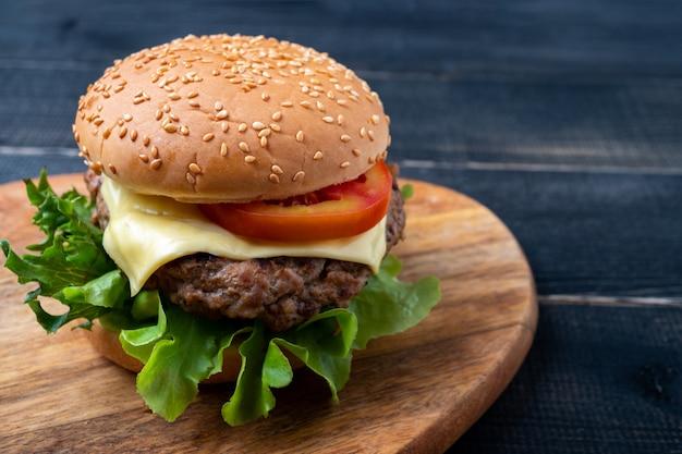 新鮮な野菜、レタス、トマト、まな板の上のチーズと新鮮なおいしい自家製ハンバーグ。