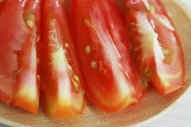 Свежие помидоры на деревянной ложкой, крупным планом