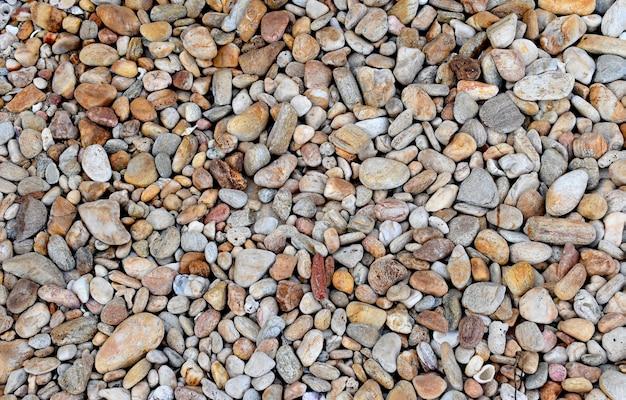 茶色の石のペブル海のビーチのテクスチャの壁紙の背景