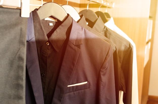 衣類のドレスルームにぶら下がっている男性のスーツジャケットの列