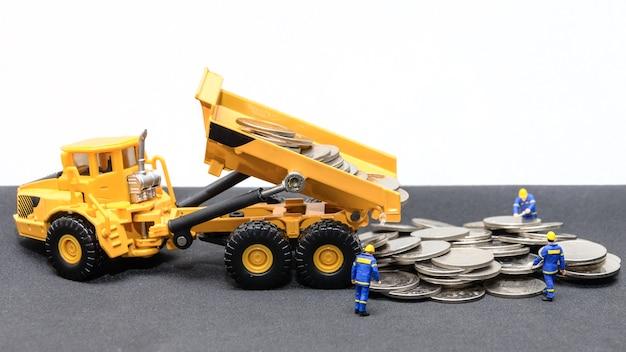トラックを持つ小型の技術者チームは、地面にコインをダンプする