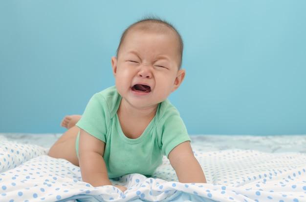 ベッドの上の動揺の泣いている赤ちゃんアジア男の子の肖像画