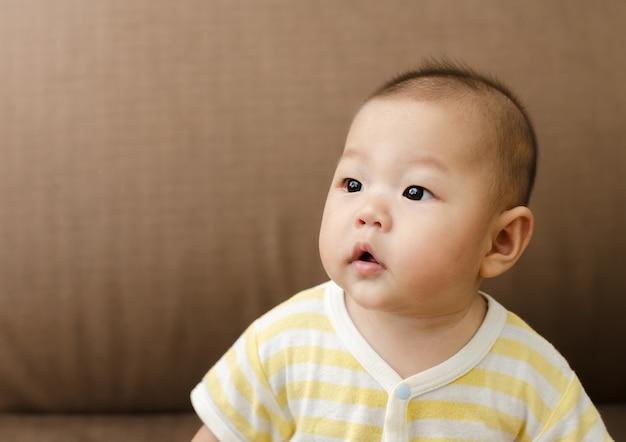 座っていると左側を見て小さな小さなアジアの赤ちゃん幼児の肖像画
