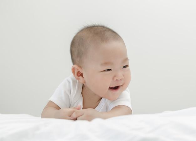 小さな小さなアジアの幸せな赤ちゃん幼児リラックスしてベッドの中で笑顔