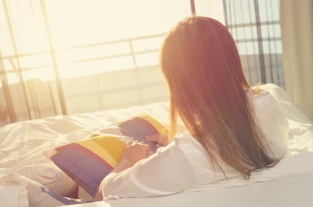 ベッドに座ってリラックスするパジャマの女性