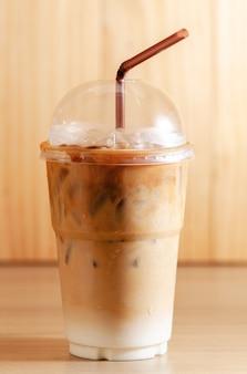 木製の背景にプラスチックガラスを取るアイスコーヒーラテ