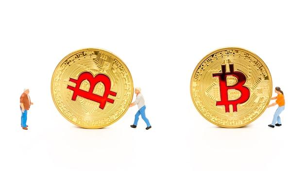 ゴールデンビットコインコインを転がしているミニチュア男