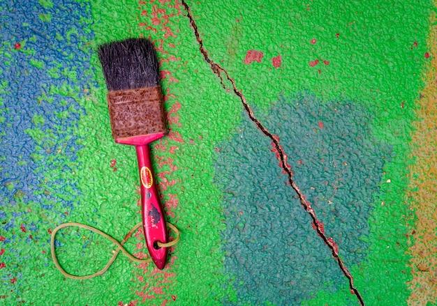 古い錆ついた大工は、色とりどりの埃っぽい割れたコンクリートの表面の床にブラシを塗る
