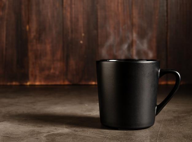 暗い木の背景と黒のマグカップでコーヒー