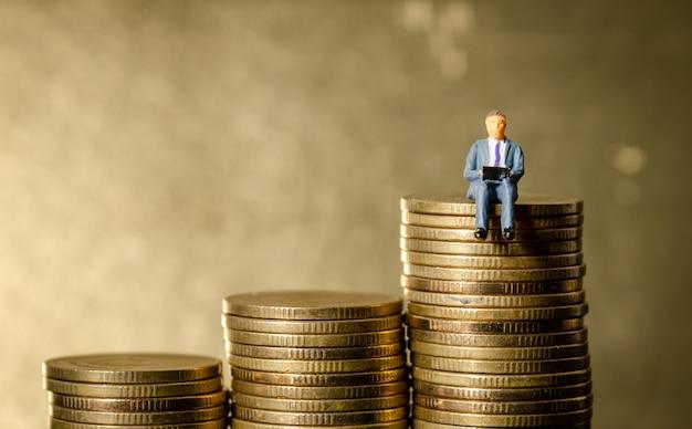 ゴールドコインの積み重ねの上に座っているビジネスマン
