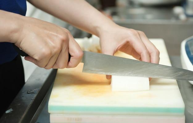 シェフ、ナイフで野菜を切る