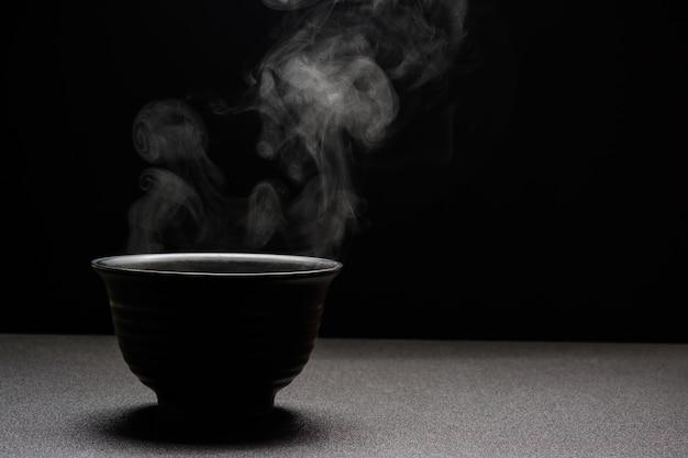 Суп горячий в черном шаре на деревянном столе, паре еды и космосе экземпляра, селективном фокусе. концепция свежей еды