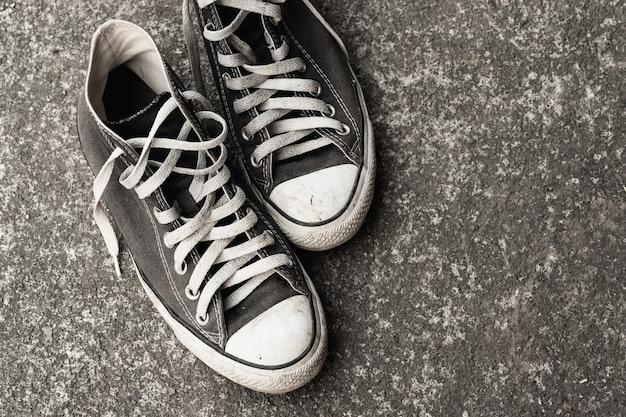 Старые тапки на цементной земле. стилистика и модные аксессуары мужчины носят обувь концепция
