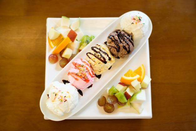 Пять шариков мороженого в длинной тарелке на столе