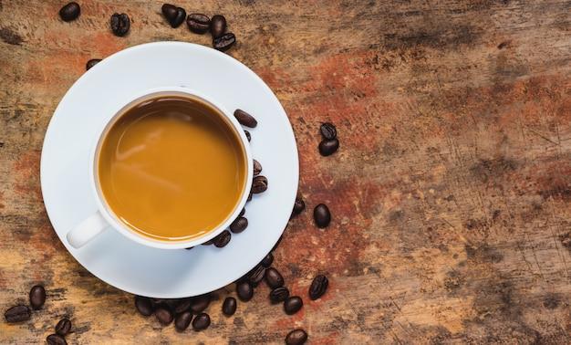 カップとコピースペースを持つテーブルの上のコーヒー豆のコーヒー