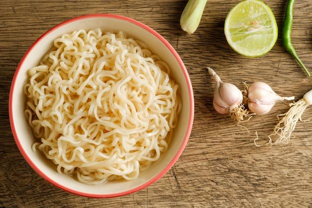 Чашка лапши быстрого приготовления, помещенная на деревянный стол с лаймом, чили, лимонной травой и чесноком в качестве ингредиентов, вид сверху лапши