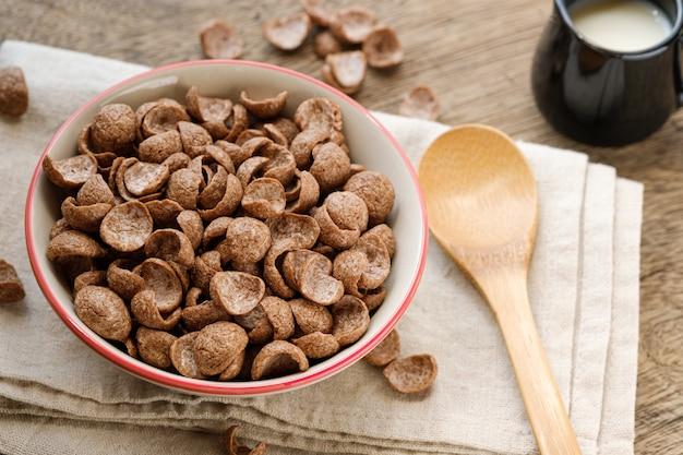 木製のテーブルの上にボウルにシリアル朝食ココア味