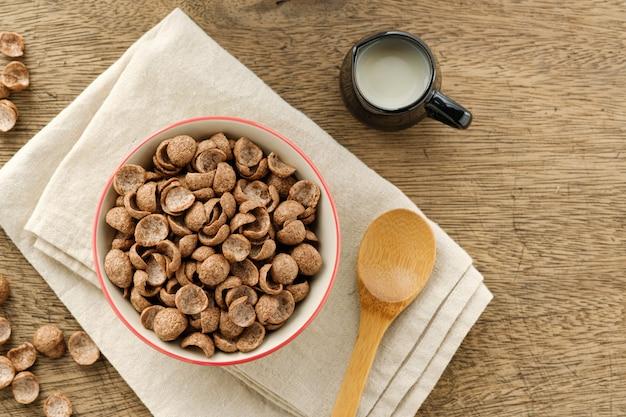 Хлопья какао завтрак зерновых в миску на деревянном фоне с копией пространства, вид сверху