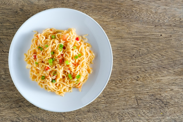 麺は木製のテーブルの上に置かれた丸い白い皿にあります。コピースペース