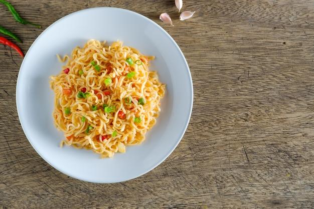麺は木製のテーブルの上に置かれた丸い白い皿の中にあります。コピースペース