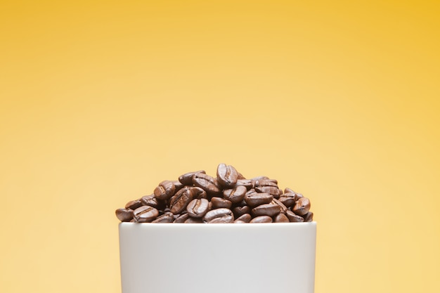 黄色に分離された白いカップのコーヒー豆