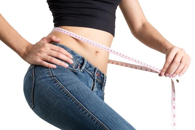 彼女のウエストを測定する女性は、体重を減らし、健康的な体のコンセプトを白い背景にします。