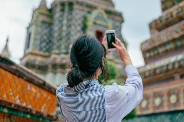 Азиатские женщины соло путешественники используют смартфон, чтобы сфотографировать древние здания пагоды